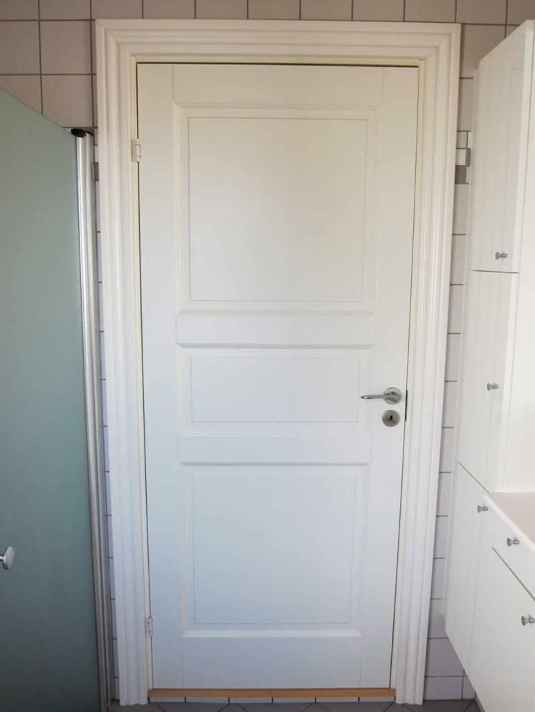 En ny badeværelsesdør opsat af en tømrer og snedker