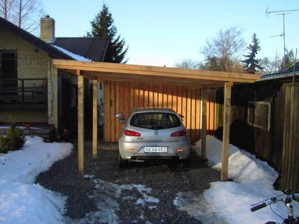 Carport i træ med tag og en grå bil